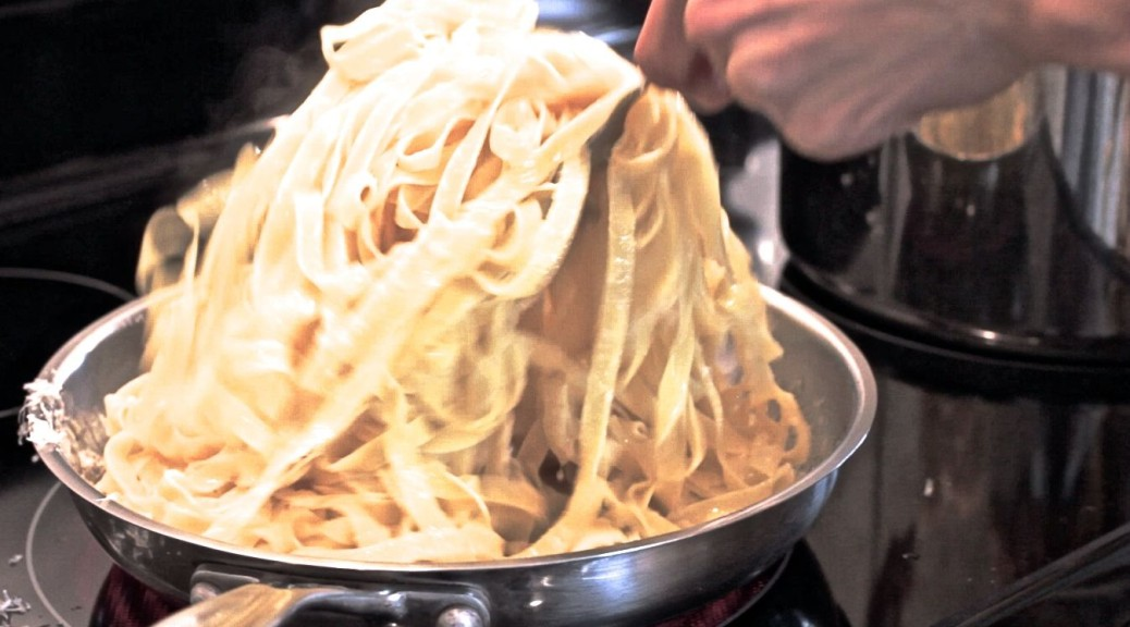 tossing fettuccine alfredo in the skillet